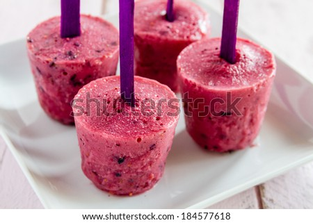 Four fresh fruit popsicles made with blueberries, raspberries and yogurt standing on white square plate - stock photo