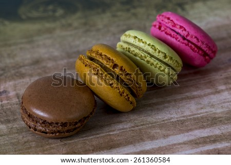 four fresh home made macarons on table top - stock photo