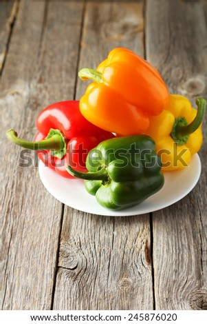 Four fresh pepper on plate on grey wooden background