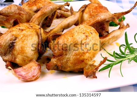 Four fried quail with gravy, rosemary and garlic, close up