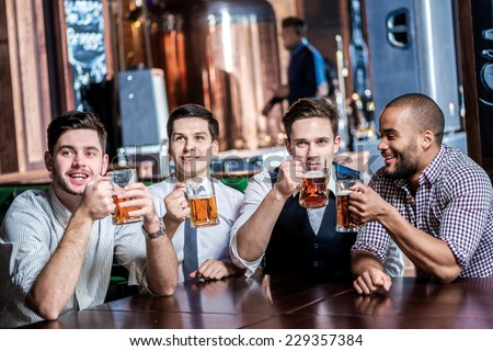 Four friends businessmen drink beer and enjoyed watching the TV in the bar. Cheerful businessmen friends having fun together in the bar with a beer watching football on TV - stock photo