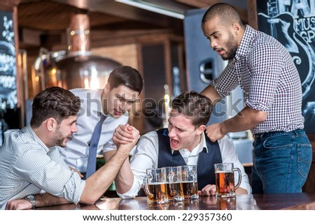 Four friends compete at the hands of drink beer and spend time together, laughing at the bar. Confident businessmen having fun with friends at the bar with a beer at the table - stock photo