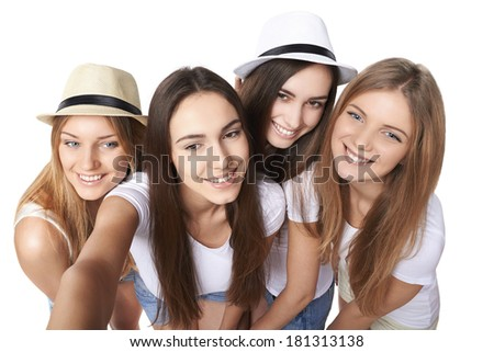 Four friends girls making self portrait with a smartphone, over white background