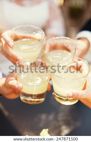 four friends holding sweet lemonade - stock photo