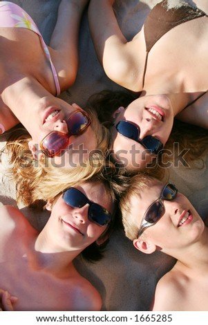 Four friends lying on beach - close up - stock photo