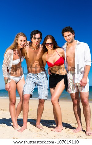 Four friends - men and women - on the beach having lots of fun in their vacation