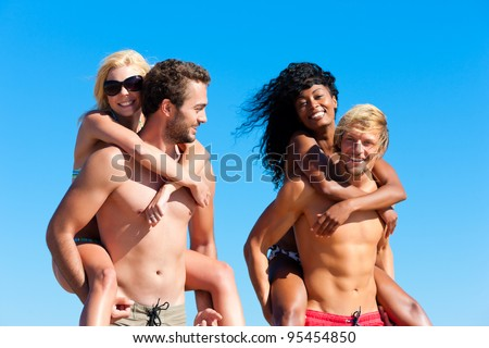 Four friends - men and women - on the beach having lots of fun, the men carrying the women pack back