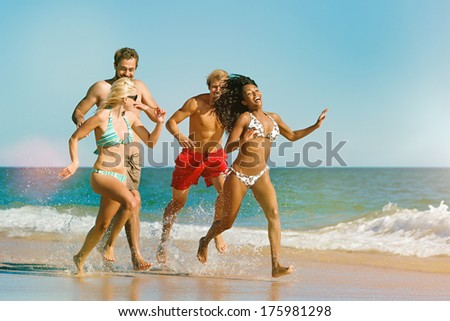 Four friends - men and women - on the ocean beach having lots of fun in their vacation running through the water