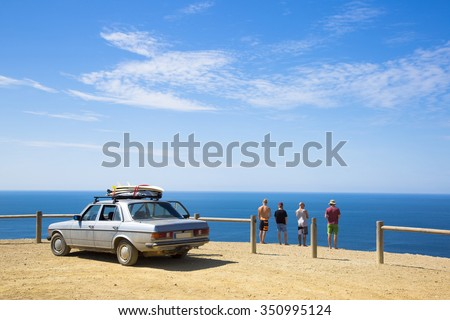 four friends on rock looking for surfing waves - stock photo