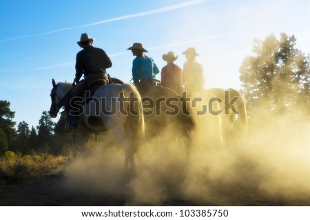 Four friends out for a evening horseback ride at sunset - stock photo