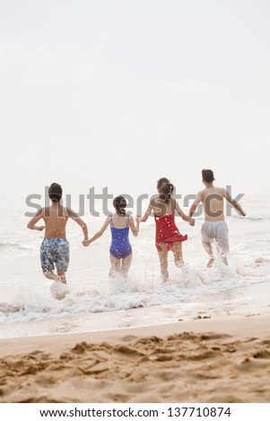 Four friends running into the water on a sandy beach, rear view