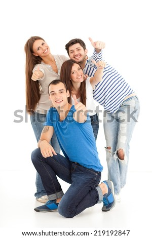 Four friends standing and smiling on white. Showing thumbs up.