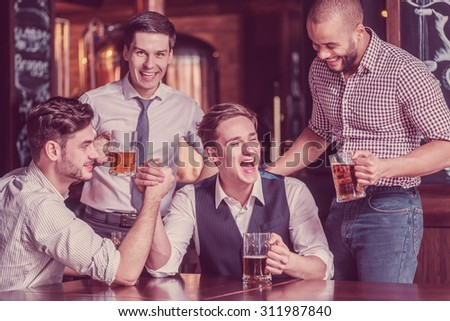 Four friends struggle on their hands drink beer and spend time together, laughing at the bar. Confident businessmen having fun with friends at the bar with a beer at the table - stock photo