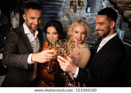 Four friends with champagne glasses celebrating and toasting in restaurant