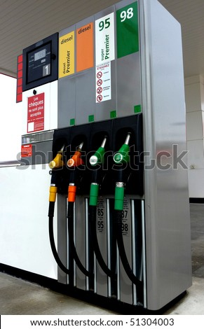 Four gas pump nozzles on a petrol station - stock photo