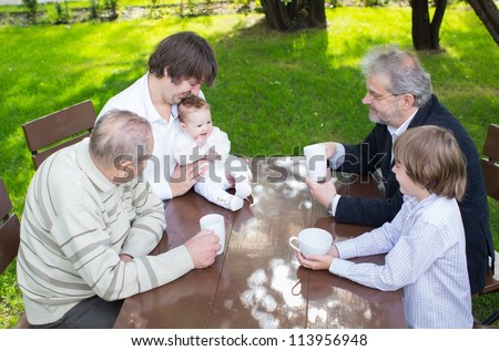 Four generations of one family sitting at a wooden table in the garden drinking coffee and tea - stock photo
