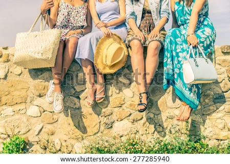 Four girlfriends sitting on a wall outdoors with spring and summer dresswear - Women meeting and having fun in a countryside - Concepts about friendship,seasonal,lifestyle and shopping - stock photo