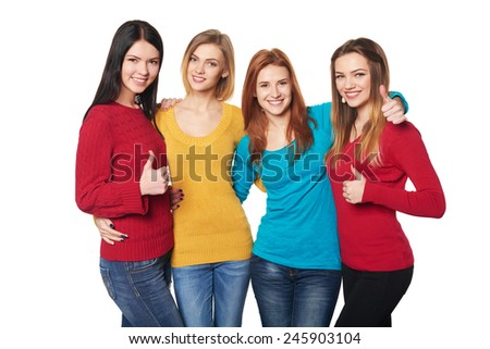 Four girls friends gesturing thumbs up over white background - stock photo