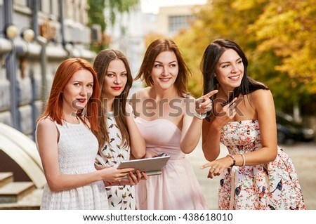 four girls friends toursits looking with tablet pc - stock photo