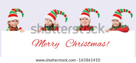 Four girls in suits of Christmas elf with white banner - stock photo
