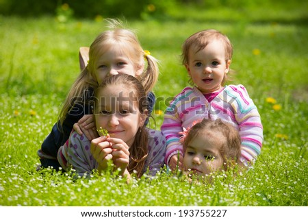 four girls lying on grass outdoors
