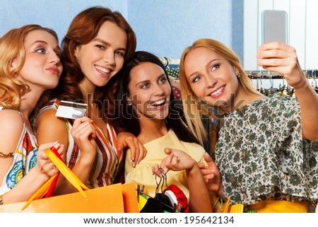 Four girls making photo with mobile camera in shop