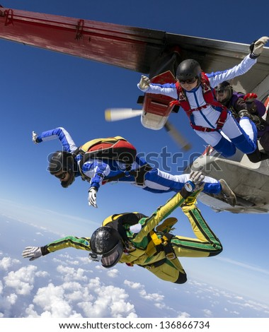 Four girls parachutists jump out of an airplane. - stock photo