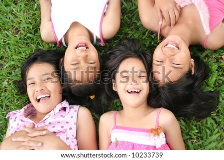 Four girls playing in the park. - stock photo
