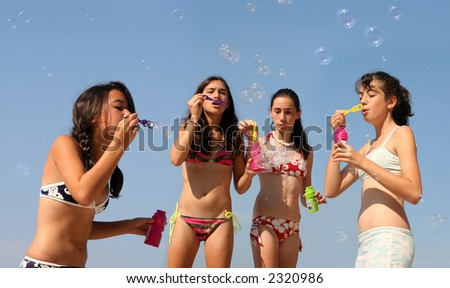Four girls playing with bubbles on the beach