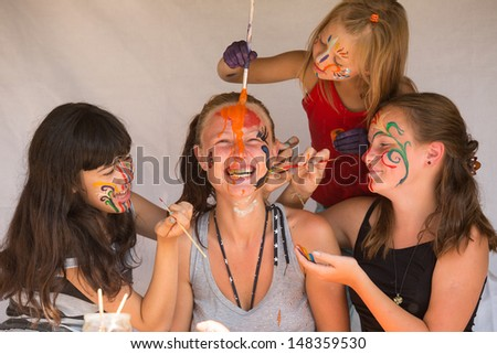 Four girls playing with painting  - stock photo