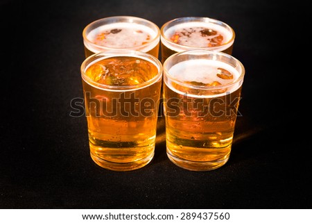 Four glasses of beer seen from above - stock photo