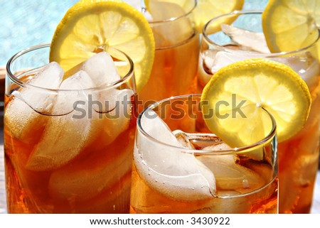 Four glasses of lemon ice tea, outside by the pool.
