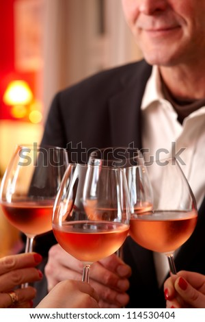 Four glasses of wine being clinked together as a toast at a celebration or function - stock photo