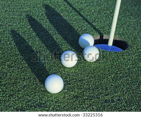four golf balls heading toward cup on green - stock photo