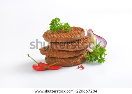 four grilled beef burgers with onion and chili peppers, decorated with pieces of parsley