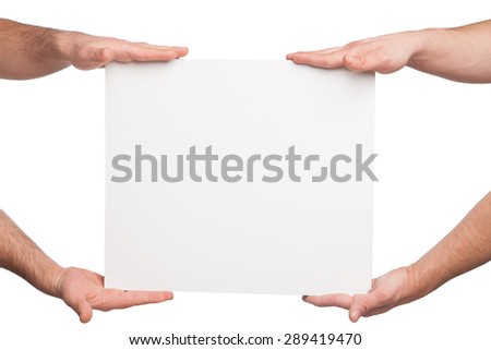 four hands holding a blank white board - stock photo