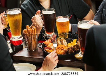 four Hands holding beer glasses drinking together in the pub - stock photo