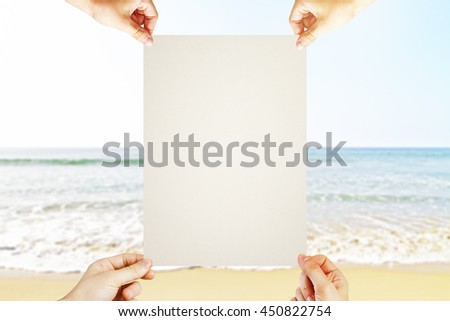 Four hands holding blank poster on seaside background. Mock up - stock photo