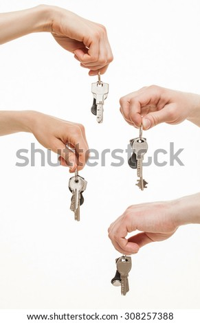 Four hands holding bunches of keys, white background - stock photo