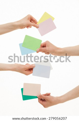 Four hands holding colorful paper cards, white background