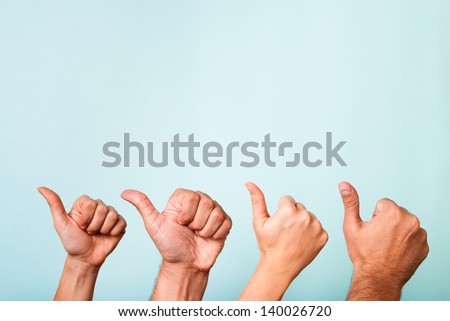 Four hands making like, recommend, success gesture with thumbs up. Content marketing satisfaction concept. The hands have different skin tones. - stock photo