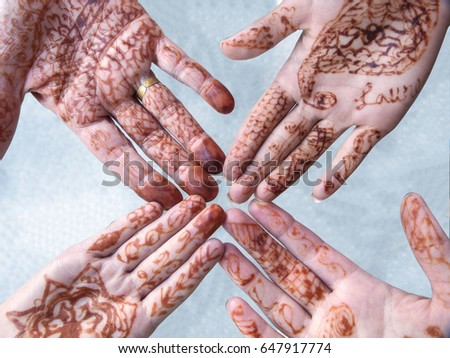 Four hands touching fingers. The hands are tattooed with henna in preparation for a wedding