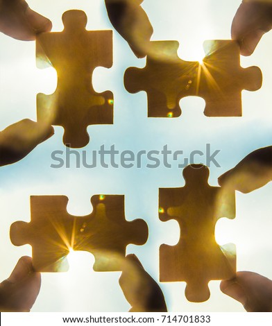 four hands trying to connect couple puzzle piece with sunset background. empty space. Jigsaw wooden puzzle against sun rays. two part of whole. symbol of association and connection. business strategy