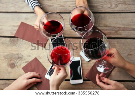 Four hands with smart phones holding glasses with red wine, on wooden table background - stock photo