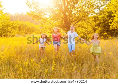 four happy beautiful children running playing moving together in the beautiful summer day. jumping and looking at camera with happiness and toothy smile.