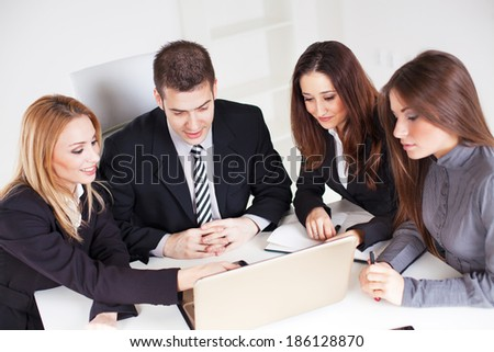 Four happy Business people looking project at laptop in the office. - stock photo