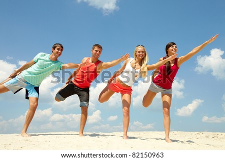 Four happy friends doing exercise on the beach - stock photo