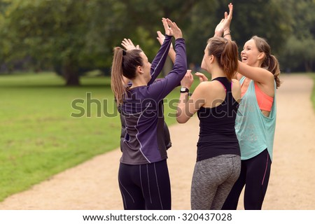 Four Happy Healthy Women Giving Double High Five Gesture While Relaxing After an Outdoor Exercise at the Park. - stock photo