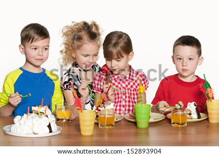 Four happy kids celebrate a birthday at the table