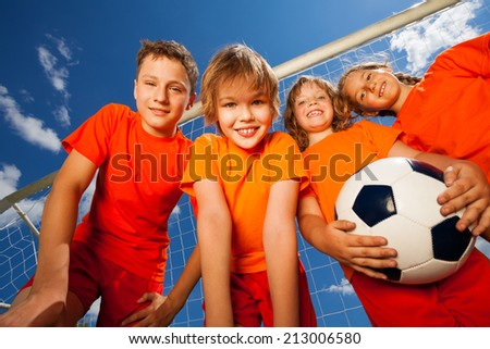 Four happy kids with football portrait - stock photo